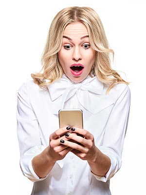 Woman looking surprised at her cell phone.