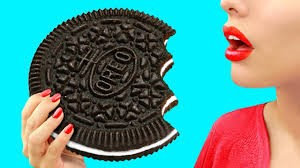 Image of women about to eat large oreo cookie