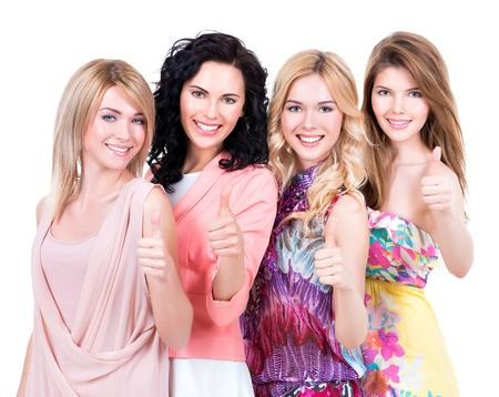 """Four women smiling and giving """"thumbs up"""" to the camera."""